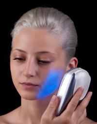Frau therapiert ihre Gesichtshaut mit blauem Licht.