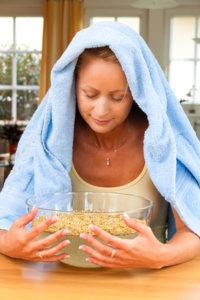 Frau mit Dampfbad gegen Pickel